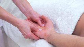 Mãos fêmeas que fazem a massagem de relaxamento da palma para o paciente masculino na sala terapêutica video estoque