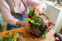 Mãos fêmeas que fazem o ramalhete bonito das flores no fundo imagens de stock