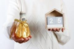 Mãos fêmeas que guardam a caixa de presente do Natal com dólar e calendário, xmas 25 Desember Fundo Presente de época natalícia e Imagens de Stock