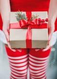 Mãos fêmeas que guardam a caixa de presente do Natal com fita vermelha, ramo Imagens de Stock Royalty Free