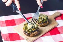 Mãos fêmeas que guardam a faca e a forquilha e que cortam a refeição Cogumelos com queijo em uma toalha de mesa aperitivo Fundo d Foto de Stock
