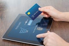 Mãos fêmeas que guardam o cartão de crédito e uma tabuleta no escritório e Foto de Stock