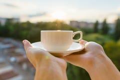 Mãos fêmeas que guardam o copo branco clássico com pires, por do sol da noite do fundo, silhueta da cidade, hora dourada imagem de stock royalty free