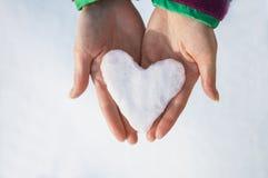 Mãos fêmeas que guardam o coração da bola de neve Imagens de Stock