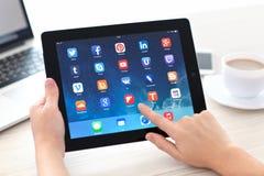 Mãos fêmeas que guardam o iPad com meios sociais app na tela dentro