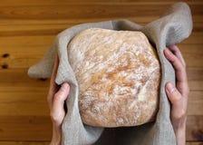 Mãos fêmeas que guardam o pão na tela de linho fotografia de stock