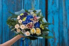 Mãos fêmeas que guardam o ramalhete da beleza de rosas vermelhas foto de stock