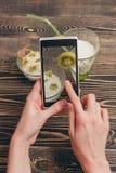 Mãos fêmeas que guardam o smartphone Imagem de Stock
