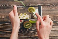 Mãos fêmeas que guardam o smartphone Fotografia de Stock