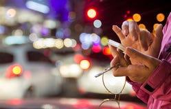 Mãos fêmeas que guardam o smartphone da tela vazia imagem de stock