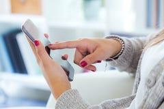 mãos fêmeas que guardam o smartphone em casa Foto de Stock Royalty Free