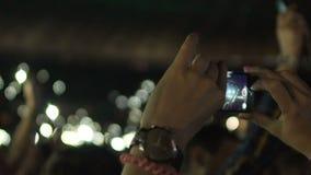 Mãos fêmeas que guardam o smartphone, mulher no vídeo do película da multidão de evento surpreendente vídeos de arquivo