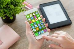 Mãos fêmeas que guardam o telefone branco com apps dos ícones da tela home Foto de Stock