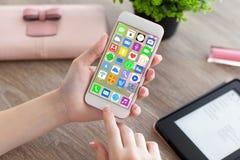 Mãos fêmeas que guardam o telefone branco com apps dos ícones da tela home Fotos de Stock