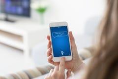 Mãos fêmeas que guardam o telefone com o assistente pessoal do app na tela imagem de stock royalty free