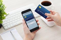 Mãos fêmeas que guardam o telefone com a carteira móvel para a compra em linha imagem de stock royalty free