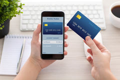 Mãos fêmeas que guardam o telefone com a carteira móvel para a compra em linha fotos de stock royalty free