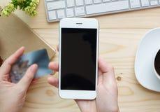 Mãos fêmeas que guardam o telefone com tela vazia Fotos de Stock