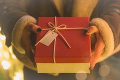 Mãos fêmeas que guardam um presente imagens de stock