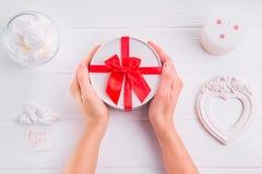 Mãos fêmeas que guardam um presente para o dia do ` s do Valentim Cartão com amor você palavras, doces, vela e quadro do handwrit Imagem de Stock
