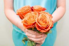Mãos fêmeas que guardam um ramalhete com flores Rosas vermelhas nas mãos da menina Fundo para o cart?o imagens de stock royalty free