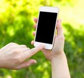 Mãos fêmeas que guardam um telefone branco imagens de stock