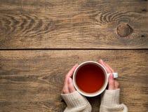 Mãos fêmeas que guardam uma caneca de chá preto quente inverno frio w branco Imagem de Stock Royalty Free