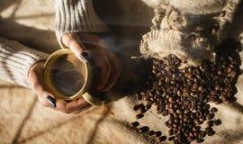 Mãos fêmeas que guardam uma xícara de café com espuma sobre a tabela de madeira, vista superior Fotos de Stock Royalty Free