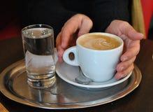 Mãos fêmeas que guardam a xícara de café no café Fotos de Stock Royalty Free