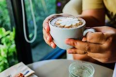 Mãos fêmeas que guardam xícaras de café Imagem de Stock Royalty Free