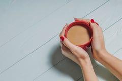 Mãos fêmeas que guardam xícaras de café sobre o fundo de madeira, Fotografia de Stock Royalty Free