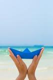 Mãos fêmeas que jogam com o barco do papel azul na praia imagens de stock