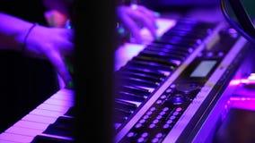 Mãos fêmeas que jogam o piano elétrico sob a iluminação colorida da fase, close-up vídeos de arquivo