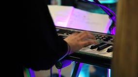Mãos fêmeas que jogam o piano elétrico sob a iluminação colorida da fase, close-up video estoque