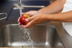 Mãos fêmeas que lavam a maçã com água no dissipador Foto de Stock