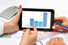 Mãos fêmeas que leem colunas do negócio na tabuleta, na mesa de escritório Fotos de Stock