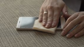 Mãos fêmeas que limpam o telefone celular de superfície da tela com o fim de pano acima video estoque