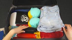 Mãos fêmeas que põem coisas do verão em uma mala de viagem Os braços da embalagem da jovem mulher ensacam com material pessoal pa filme