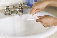 Mãos fêmeas que põem a pasta de dente sobre a escova de dentes Fotografia de Stock