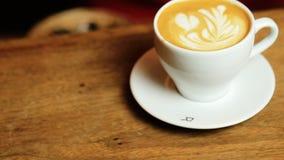 Mãos fêmeas que põem uma xícara de café branca sobre uma placa filme
