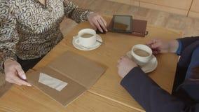 Mãos fêmeas que pagam a conta do café com cartão de crédito video estoque
