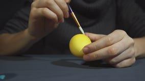 Mãos fêmeas que pintam a decoração do ovo para easter sobre um fundo cinzento filme