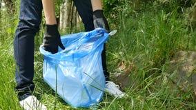 Mãos fêmeas que recolhem o lixo plactic no pacote azul Limpeza da natureza, voluntário da ecologia, conceito verde filme