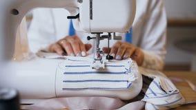 Mãos fêmeas que trabalham na máquina de costura video estoque
