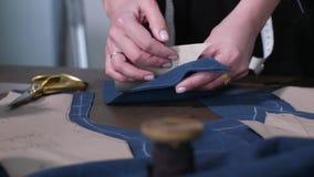 Mãos fêmeas que unpinning o papel do teste padrão cortado video estoque