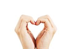 Mãos fêmeas sob a fôrma do coração Imagens de Stock Royalty Free