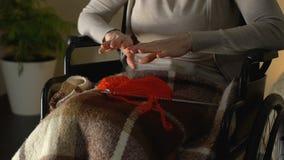 Mãos fêmeas trembling que tentam tomar agulhas de confecção de malhas, doença de Parkinsons filme