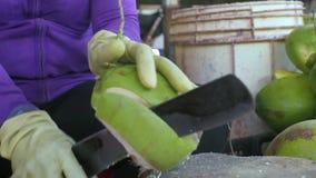 Mãos fêmeas usando a faca para descascar do fim maduro do coco acima Mulher que descasca o coco fresco para o suco bebendo filme