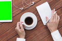 Mãos fêmeas usando o bloco de notas e a xícara de café, tabuleta do modelo e fones de ouvido digitais na mesa de madeira marrom,  fotos de stock royalty free