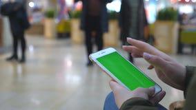 Mãos fêmeas usando o smartphone moderno com tela verde Moça que senta-se no banco no shopping e que bate em filme